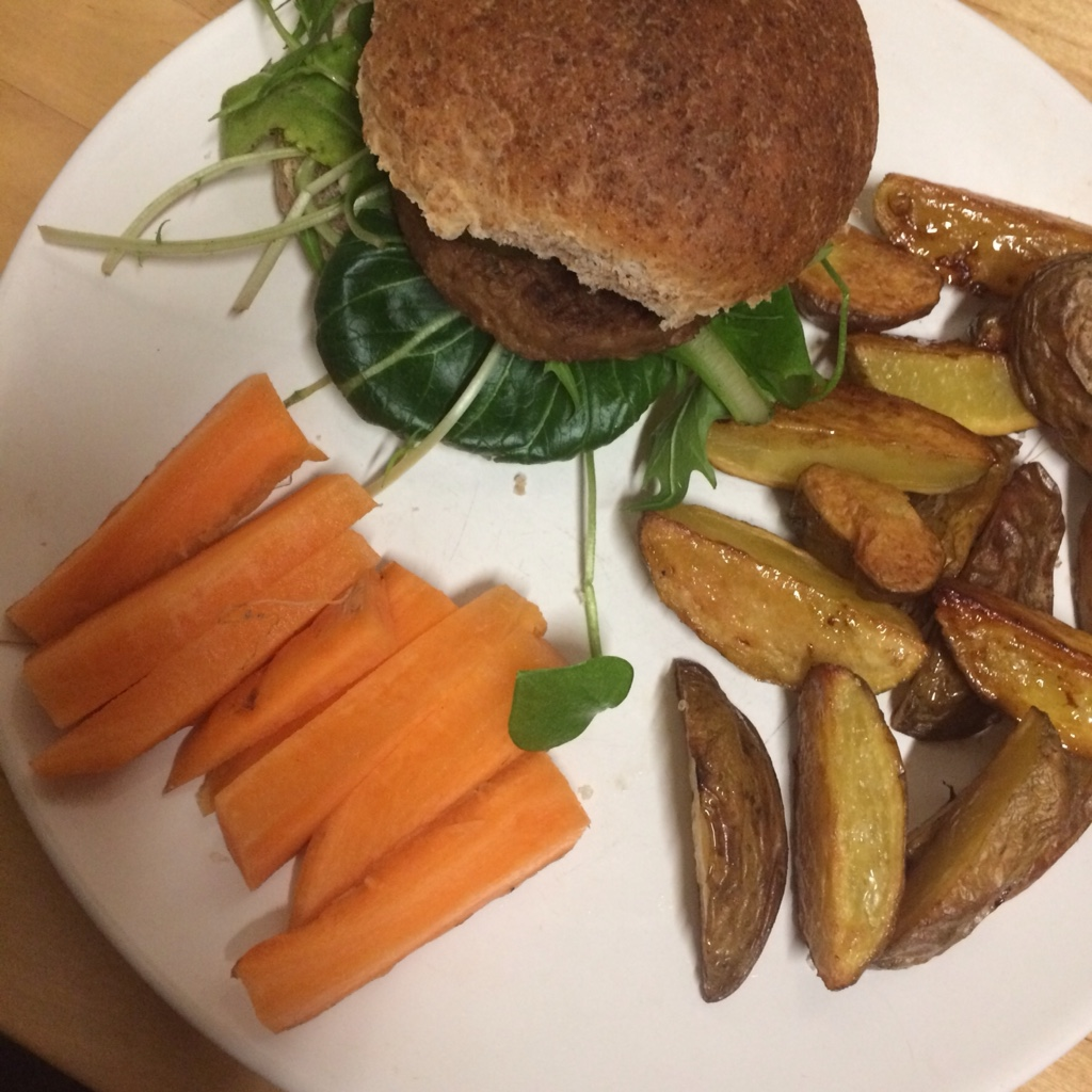 Vegetable burger in whole meal bun with green leaves and mayonnaise, potato fries and carrot sticks midorigreen.co.uk