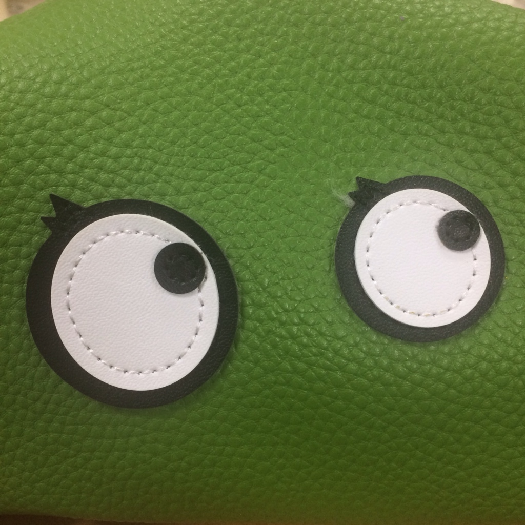 Eye shapes sewn on a green background